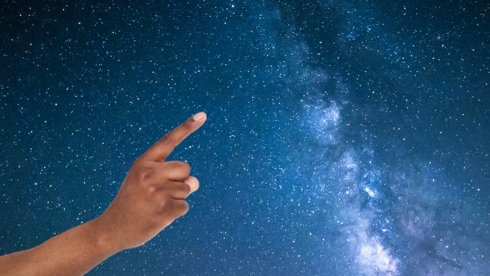 A hand pointing at stars