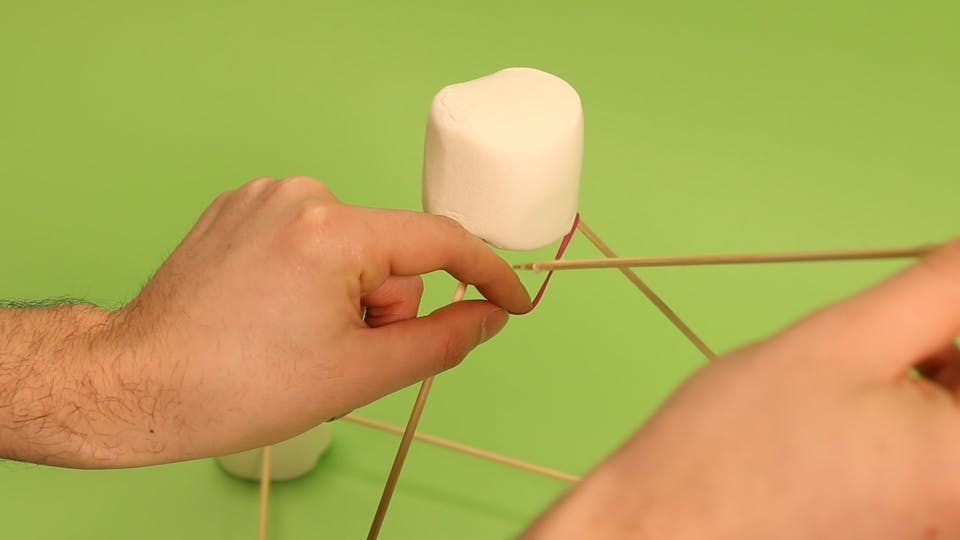 Stick the skewer (with the spoon) inside the rubber band, and poke it straight into the marshmallow at the base