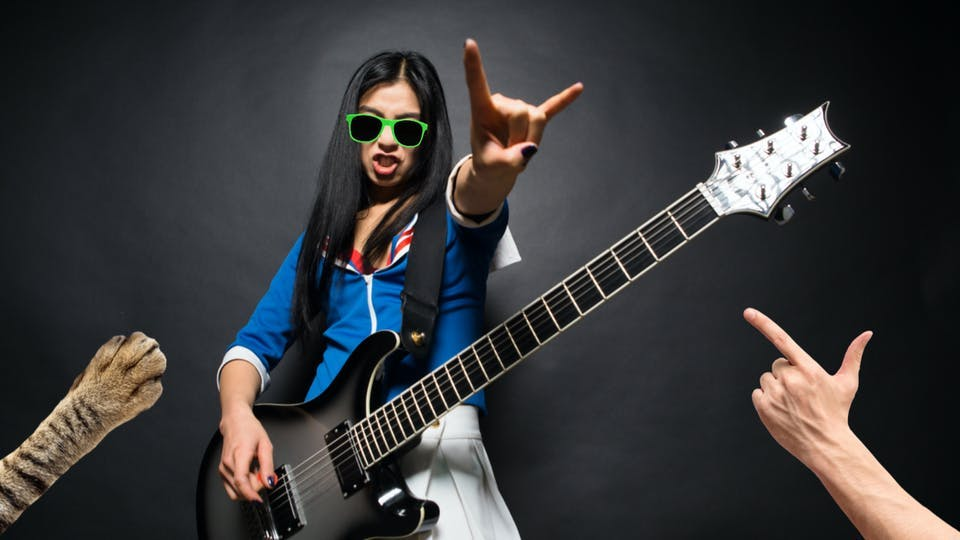 A woman playing the electric guitar