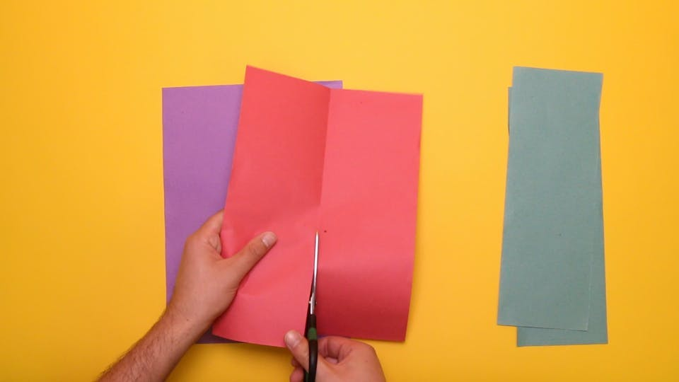 Fold each piece of paper in half, and cut down the middle, so that you get six long strips of coloured paper