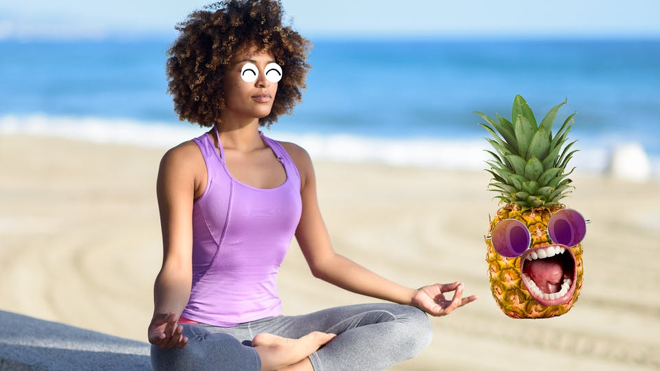 Woman meditating on beach with pineapple