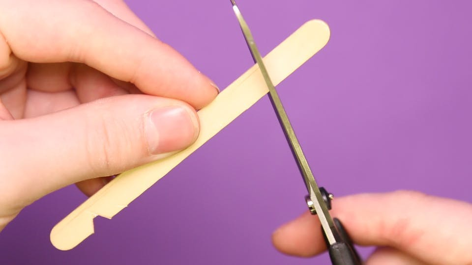 Carefully cut 2 small notches in a lollipop stick with scissors, about 1 centimetre from the end