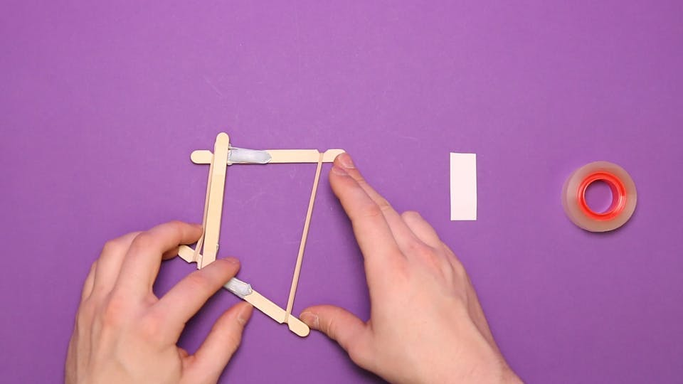 Stretch a second rubber band around the other end of the lollipop sticks