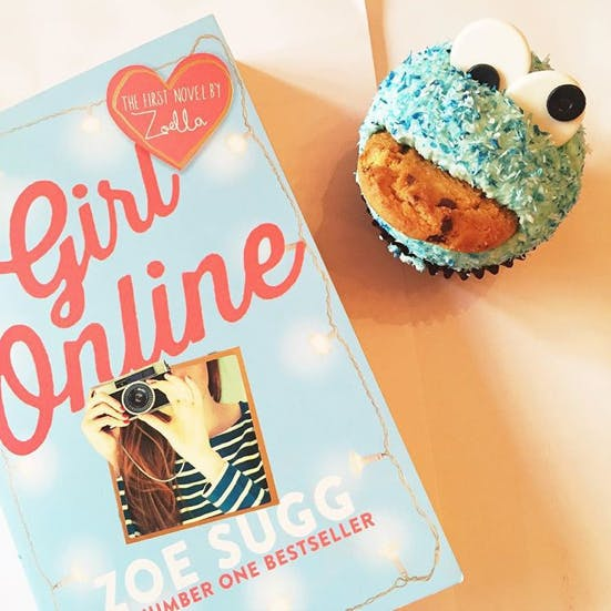 A copy of Zoella's new book sits by a cupcake which looks like Cookie Monster