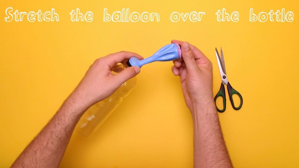 Stretch the balloon over the bottle