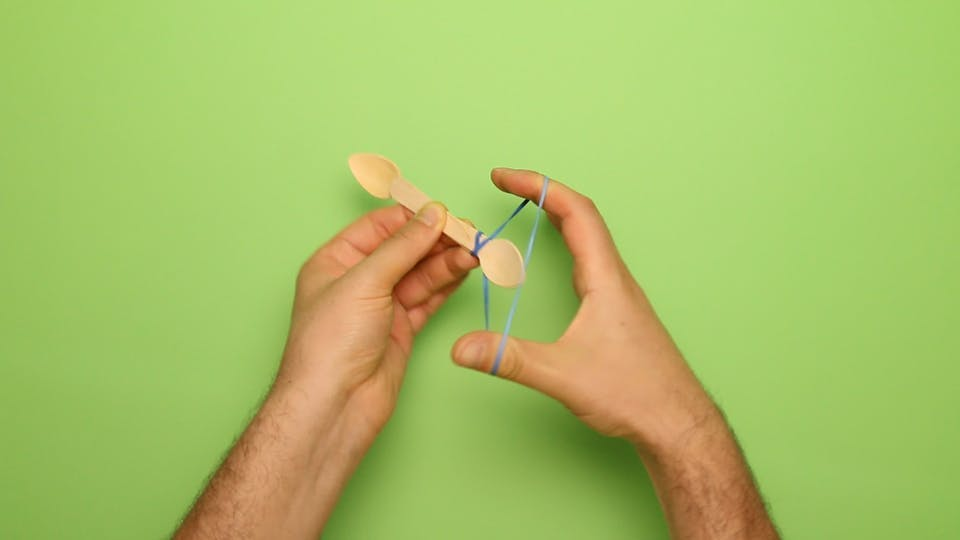 Wrap a rubber band around one end of the spoons