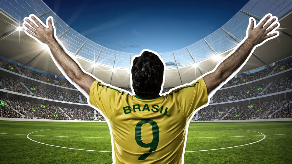 A Brazil football player raising their arms in victory