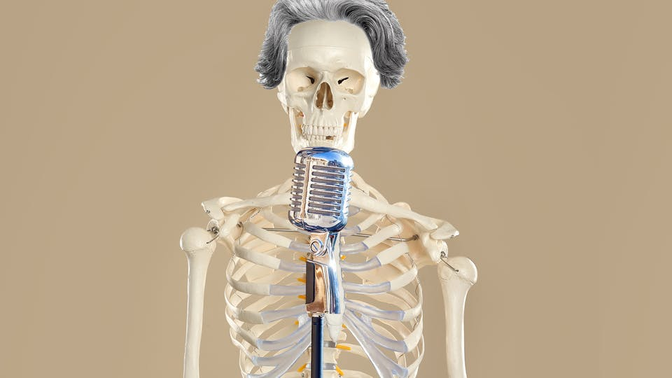 Skeleton in front of a microphone