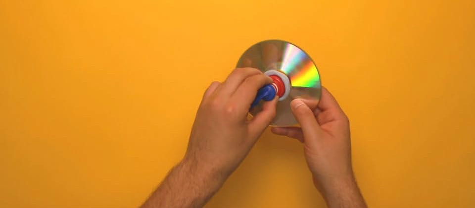 A bottle cap being fixed to the center of a CD with blu tak