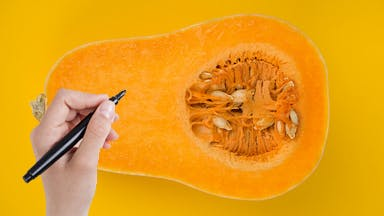 Someone writing on a slice of butternut squash
