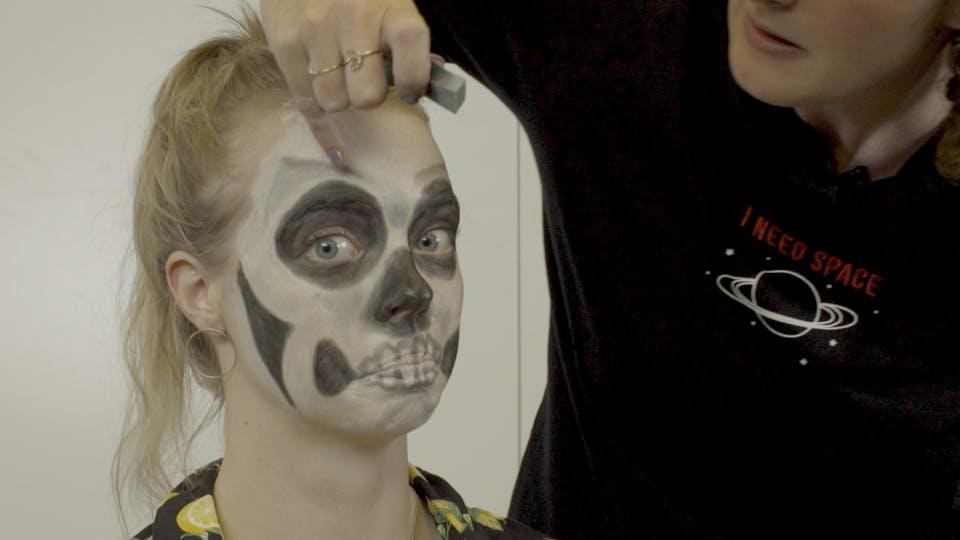 Cassie blending the makeup on Emma's face