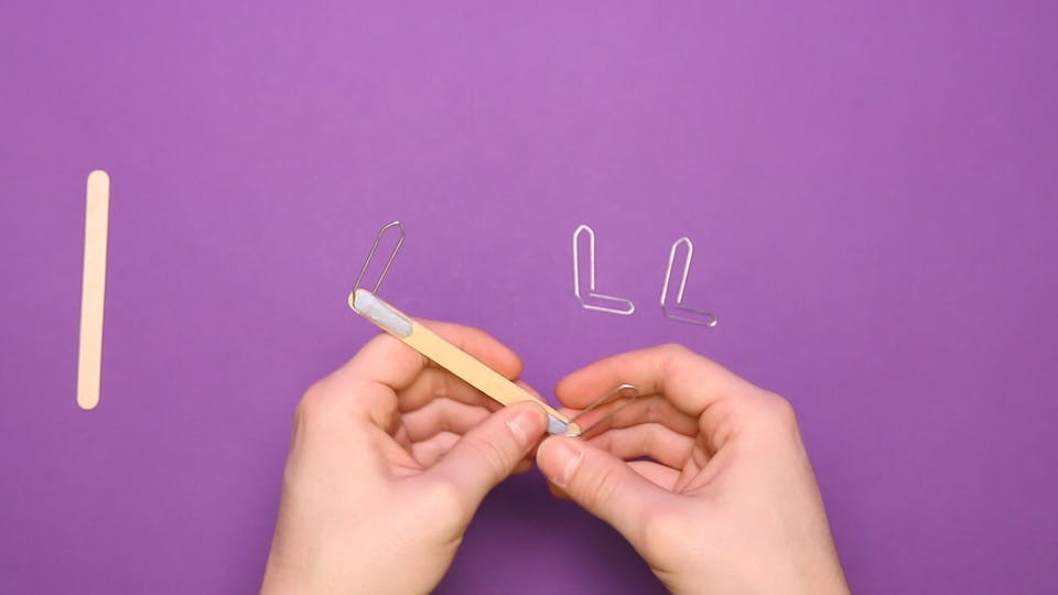 Bend 4 paperclips and attach to another lollipop stick with sticky tack