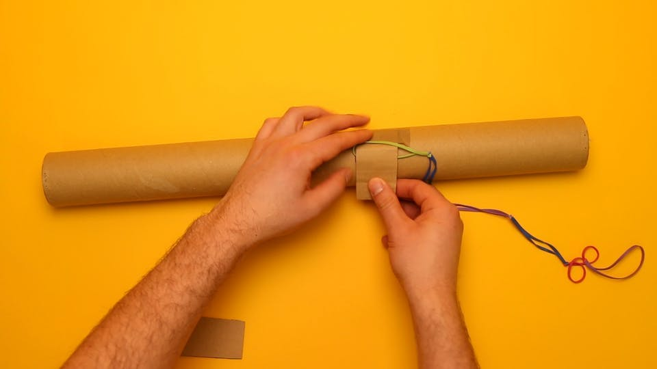 Use your 2 cardboard scraps to attach the rubber bands to the postal tube