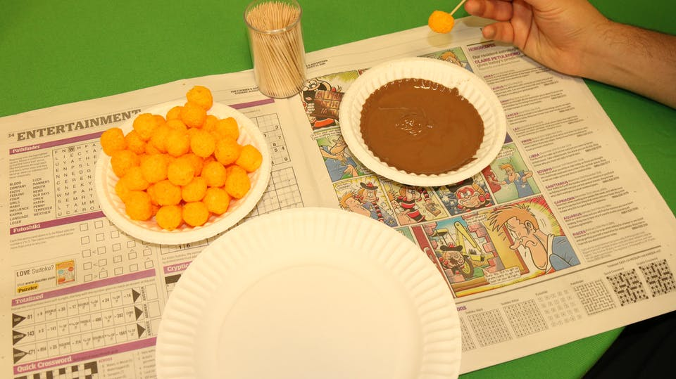 Get ready to dip your cheese puff into the chocolate, by stabbing it with a toothpick.