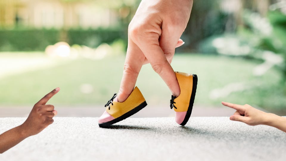 Two fingers wearing a pair of shoes and going for a stroll