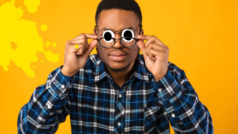Man adjusting glasses on yellow background